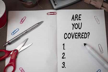 Text sign showing Are You Covered Question. Business photo showcasing asking showing if they had insurance in work or life Scissors and writing equipments plus math book above textured backdrop 写真素材