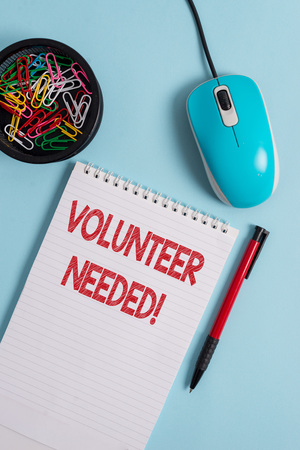 Text sign showing Volunteer Needed. Business photo text asking demonstrating to work for organization without being paid Notebook and writing equipment with computer mouse above pastel backdrop Stock Photo