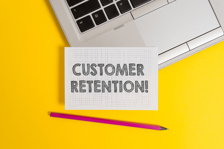 Handwriting text writing Customer Retention. Conceptual photo Keeping loyal customers Retain analysisy as possible Top trendy metallic laptop pencil squared paper sheet colored background