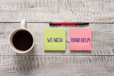 Text sign showing We Need Your Help. Business photo text asking someone to stand with you against difficulty Stationary placed next to a cup of black coffee above the wooden table Stock Photo