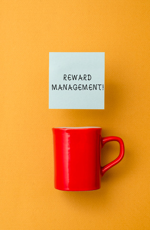 Conceptual hand writing showing Reward Perforanalysisce. Concept meaning Appraisal Recognize workers Relative Worth to the company Front view coffee cup colored sticky note yolk color background