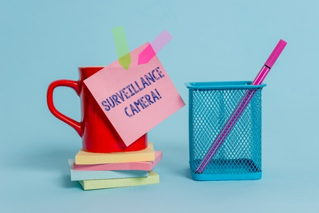 Handwriting text writing Surveillance Camera. Conceptual photo Closed Circuit Television transmit signal on monitors Cup note arrow banners stacked pads metal pen holder pastel background