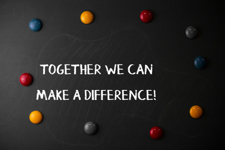 Text sign showing Together We Can Make A Difference. Business photo showcasing be very important some way in like team or group Round Flat shape stones with same sizes stick to old chalk black board