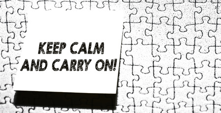 Word writing text Keep Calm And Carry On. Business photo showcasing slogan calling for persistence face of challenge Piece of square note paper use for give notation stick to puzzle background Banco de Imagens