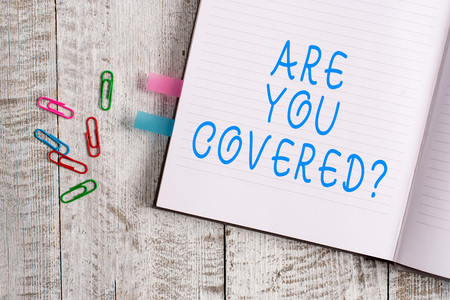 Text sign showing Are You Covered Question. Business photo text asking showing if they had insurance in work or life Thick pages notebook stationary placed above classic look wooden backdrop