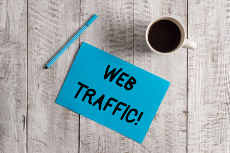 Conceptual hand writing showing Web Traffic. Concept meaning amount of data sent and received by visitors to website Pastel Colour paper and pen with coffee cup on wooden table