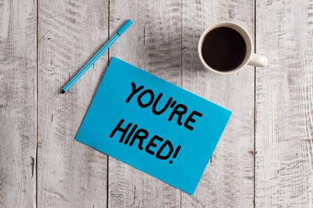 Koncepcyjne pismo ręczne pokazujące, że jesteś ponownie zatrudniony. Znaczenie pojęcia Wykorzystane przez zasoby huanalizy wskazują pracownikowi, że dostał pracę Papier w pastelowych kolorach i długopis z filiżanką kawy na drewnianym stole