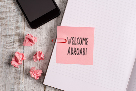 Conceptual hand writing showing Welcome Abroad. Concept meaning something that you say when someone gets on ship Notebook stationary placed above classic wooden backdrop Stock Photo
