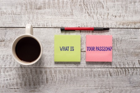 Text sign showing What Is Your Passion Question. Business photo text asking about his strong and barely controllable emotion Stationary placed next to a cup of black coffee above the wooden table