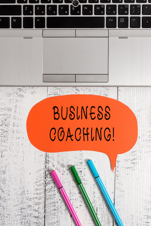 Handwriting text writing Business Coaching. Conceptual photo Helping employees become more active Consulting an expert Open laptop blank speech bubble pens ballpoints lying vintage wooden table