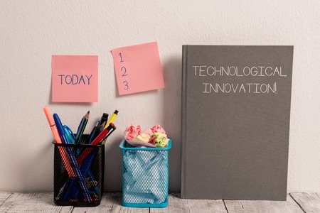 Text sign showing Technological Innovation. Business photo showcasing New Invention from technical Knowledge of Product Stick Pad Notes on Wall Two Pencil Pots Hardcover Notebook on Work Desk