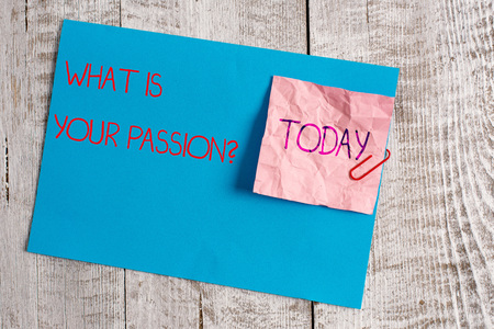 Handwriting text What Is Your Passion Question. Conceptual photo asking about his strong and barely controllable emotion Wrinkle paper and cardboard plus stationary placed above wooden background