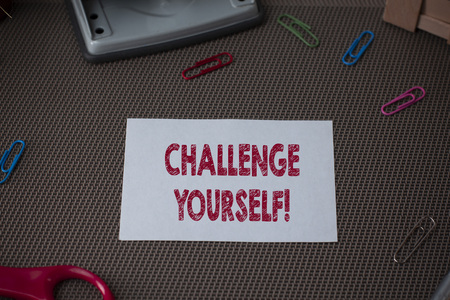 Conceptual hand writing showing Challenge Yourself. Concept meaning Setting Higher Standards Aim for the Impossible Scissor and writing equipments sheet above textured backdrop