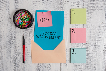Writing note showing Process Improvement. Business concept for Optimization Meet New Quotas Standard of Quality Envelope letter sticky note ballpoint clips on wooden background Archivio Fotografico