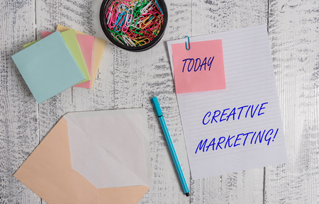 Handwriting text writing Creative Marketing. Conceptual photo Campaigning to meet the advertising requirements Envelope sheet paper sticky note pads pen clips holder wooden background Imagens