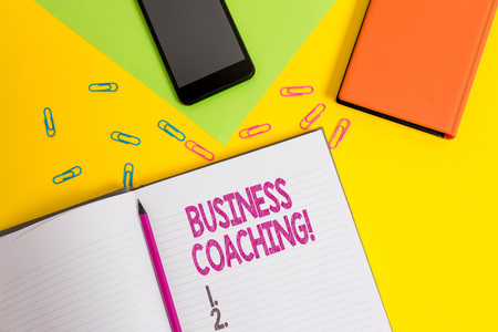 Handwriting text Business Coaching. Conceptual photo Helping employees become more active Consulting an expert Blank paper sheet pencil clips smartphone two notepads colored background
