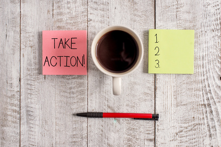 Writing note showing Take Action. Business concept for do something official or concerted to achieve aim with problem Stationary placed next to a cup of black coffee above the wooden table