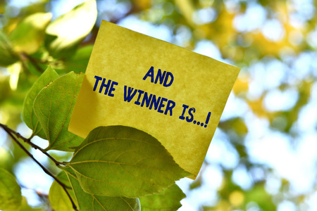 Word writing text And The Winner Is. Business photo showcasing announcing who got first place at competition or exam Piece of square paper use to give notation on tree leaf under sunny day Stockfoto