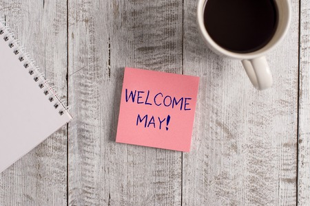 Word writing text Welcome May. Business photo showcasing welcoming fifth month of year usually considered summer Stationary placed next to a cup of black coffee above the wooden table
