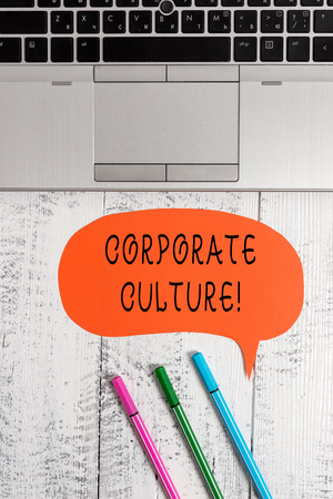 Handwriting text writing Corporate Culture. Conceptual photo Beliefs and ideas that a company has Shared values Open laptop blank speech bubble pens ballpoints lying vintage wooden table