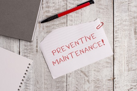 Handwriting text Preventive Maintenance. Conceptual photo Avoid Breakdown done while machine still working Torn paper and notebook sheet with a pen placed on top of wooden table Stockfoto