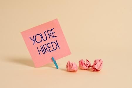 Handwriting text You Re Hired. Conceptual photo Used by huanalysis resources indicate employee that he is got job Plain note paper and stationary placed above soft pastel colour backdrop 写真素材