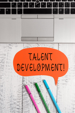 Handwriting text writing Talent Development. Conceptual photo Building Skills Abilities Improving Potential Leader Open laptop blank speech bubble pens ballpoints lying vintage wooden table