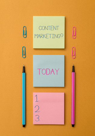 Word writing text Content Marketing Question. Business photo showcasing involves creation and sharing of online material Front view blank colored sticky note two ballpoints clips yolk background
