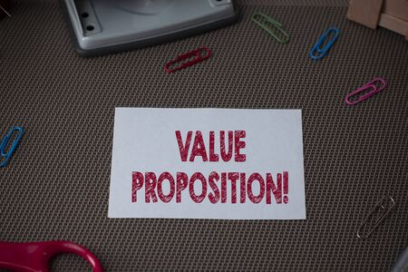 Conceptual hand writing showing Value Proposition. Concept meaning service make company or product attractive to customers Scissor and writing equipments sheet above textured backdrop