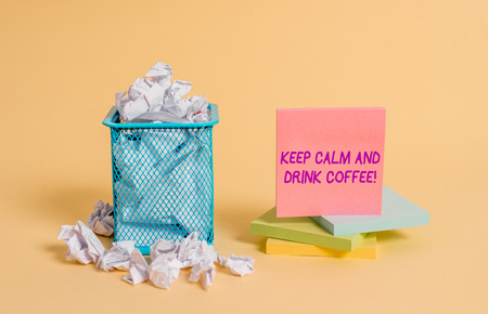 Conceptual hand writing showing Keep Calm And Drink Coffee. Concept meaning encourage demonstrating to enjoy caffeine drink and relax crumpled paper and stationary paper placed in the trash can