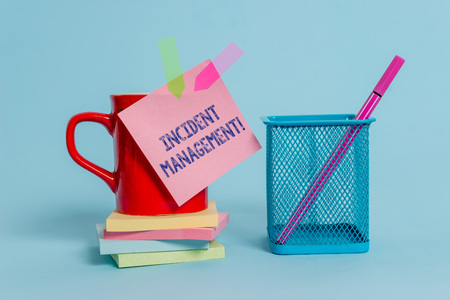Handwriting text writing Incident Management. Conceptual photo Process to return Service to Normal Correct Hazards Cup note arrow banners stacked pads metal pen holder pastel background Stok Fotoğraf