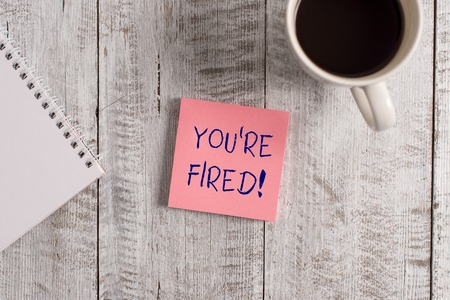 Word writing text You Re Fired. Business photo showcasing Used by boss indicate employee that he is discharged from job Stationary placed next to a cup of black coffee above the wooden table Stock Photo