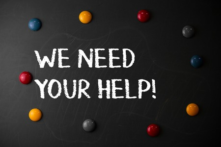 Text sign showing We Need Your Help. Business photo showcasing asking someone to stand with you against difficulty Round Flat shape stones with same sizes stick to old chalk black board