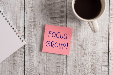 Word writing text Focus Group. Business photo showcasing showing assembled to participate in discussion about product Stationary placed next to a cup of black coffee above the wooden table
