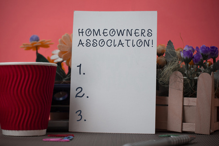 Handwriting text writing Homeowners Association. Conceptual photo Organization with fee for upkeeps of Gated Community Flowers and stationary plus plain sheet with paper big cup above a table Фото со стока
