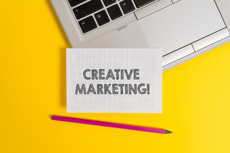 Handwriting text writing Creative Marketing. Conceptual photo Campaigning to meet the advertising requirements Top trendy metallic laptop pencil squared paper sheet colored background Imagens
