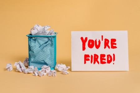 Handwriting text You Re Fired. Conceptual photo Used by boss indicate employee that he is discharged from job crumpled paper trash and stationary with empty paper placed in trash can