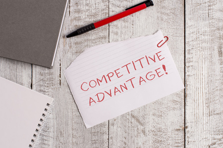 Handwriting text Competitive Advantage. Conceptual photo Company Edge over another Favorable Business Position Torn paper and notebook sheet with a pen placed on top of wooden table