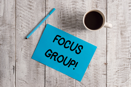 Conceptual hand writing showing Focus Group. Concept meaning showing assembled to participate in discussion about product Pastel Colour paper and pen with coffee cup on wooden table