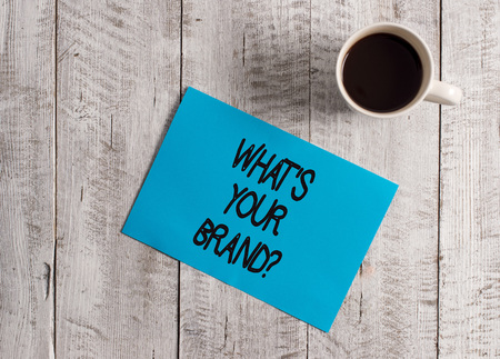 Text sign showing What S Your Brand Question. Business photo showcasing asking about product logo does or what you communicate Pastel Colour paper placed next to a cup of coffee above the wooden table