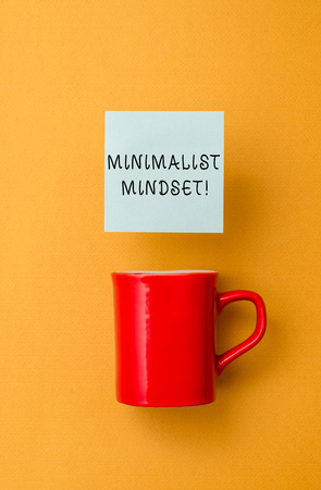 Conceptual hand writing showing Minimalist Mindset. Concept meaning Be more Aware what Life can Offer without Clutter Front view coffee cup colored sticky note yolk color background Stok Fotoğraf
