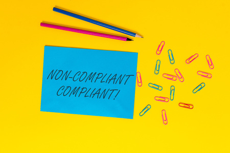 Writing note showing Non Compliant Compliant. Business concept for Resistant to the Rule in Accordance to Law Blank paper sheet message reminder pencils clips colored background