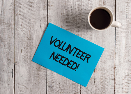 Text sign showing Volunteer Needed. Business photo showcasing asking demonstrating to work for organization without being paid Pastel Colour paper placed next to a cup of coffee above the wooden table