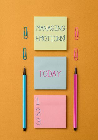 Word writing text Managing Emotions. Business photo showcasing ability be open to feelings and modulate them in oneself Front view blank colored sticky note two ballpoints clips yolk background Stock Photo