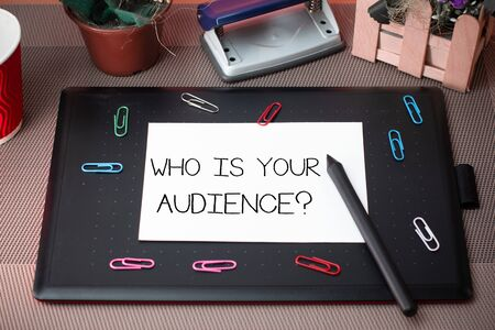 Conceptual hand writing showing Who Is Your Audience Question. Concept meaning who is watching or listening to it Scissors and equipments math book above textured backdrop Stok Fotoğraf
