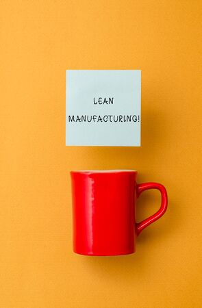 Conceptual hand writing showing Lean Manufacturing. Concept meaning Waste Minimization without sacrificing productivity Front view coffee cup colored sticky note yolk color background