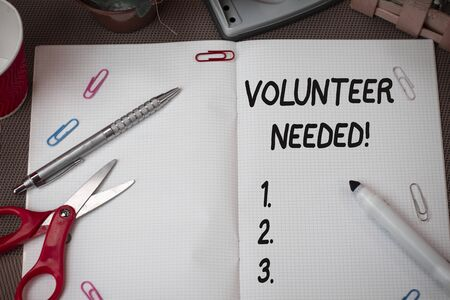 Text sign showing Volunteer Needed. Business photo showcasing asking demonstrating to work for organization without being paid Scissors and writing equipments plus math book above textured backdrop