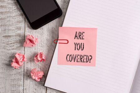 Conceptual hand writing showing Are You Covered Question. Concept meaning asking showing if they had insurance in work or life Notebook stationary placed above classic wooden backdrop