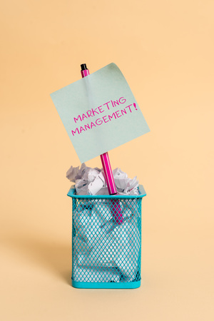 Conceptual hand writing showing Marketing Management. Concept meaning Develop Advertise Promote a new Product or Service crumpled paper and stationary with paper placed in the trash can