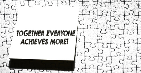Word writing text Together Everyone Achieves More. Business photo showcasing Members create synergy with strong sense mutual commitment Piece of square note paper use for give notation stick to puzzle background